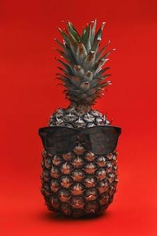 Смешной ананас в солнцезащитных очках. ананас с бокалами на красном фоне. крутой ананас.