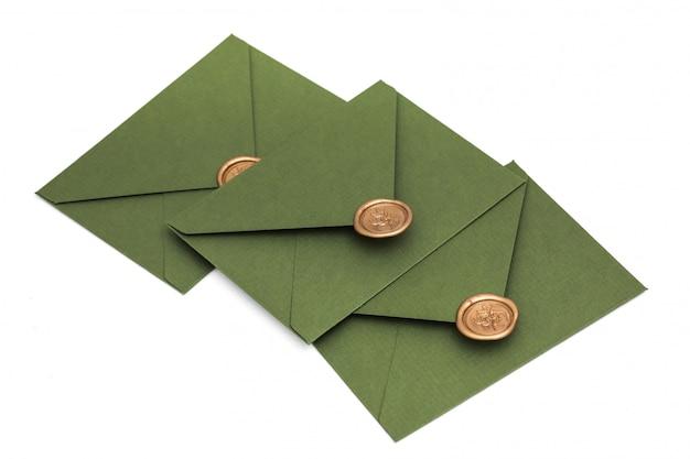 デザイナーの段ボールと白い背景の上のシールが付いている緑の封筒。シール付き封筒