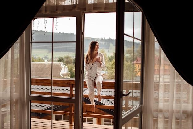 Молодая женщина на балконе, держа чашку кофе или чай утром. она в гостиничном номере смотрит на природу в шумере. девушка одета в стильные пижамы. время отдохнуть.
