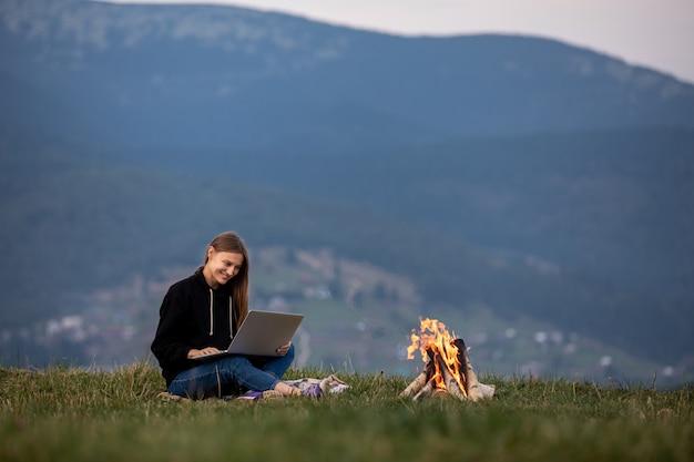 Молодая женщина с ноутбуком в горах. девушка работает, сидя на траве, костёр горит сбоку. работа, бизнес, фриланс. место для надписи.