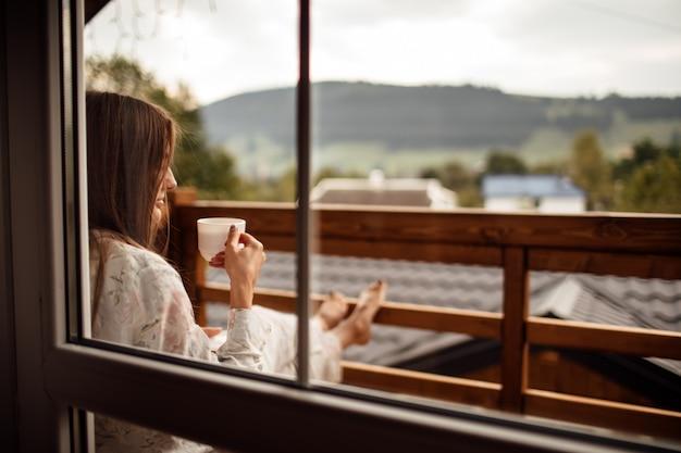 Молодая женщина на балконе, держа чашку кофе или чай утром.