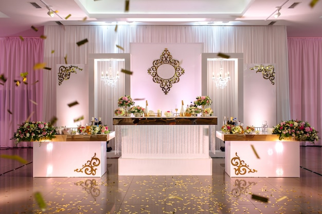 白、赤、ピンクの花と宴会場の緑の組成で飾られたお祝いテーブル。