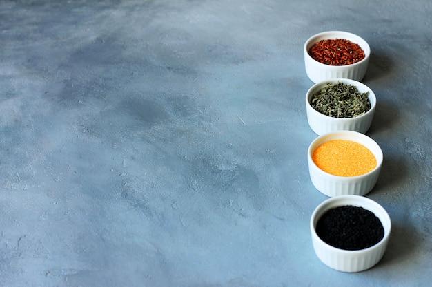 ハーブ、穀物、灰色のコンクリート背景にボウルに種