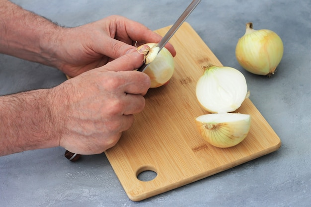 男はナイフをきれいにし、玉ねぎを切る