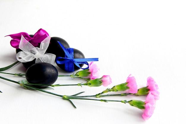 Расписные пасхальные яйца с лентами и розовыми цветами на белом фоне вид сбоку.