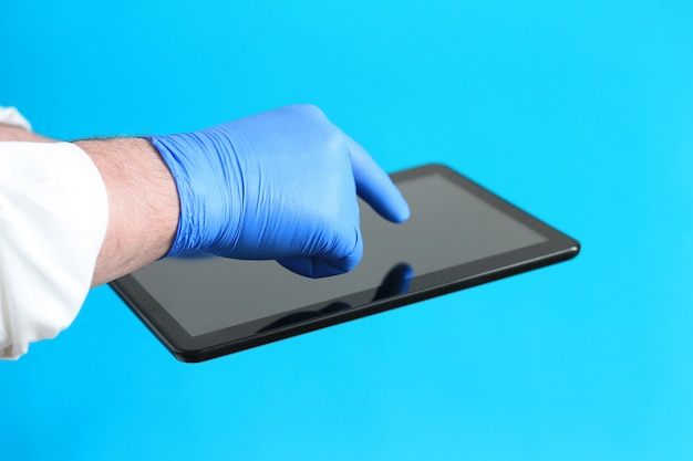 空白の黒い画面を持つ電子タブレットを保持しているラテックス滅菌手袋の医者