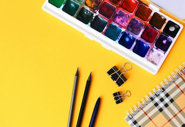 鉛筆、ノートブック、明るい黄色の背景に水彩絵の具。学校のコンセプトに戻る
