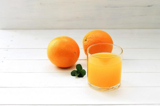 オレンジジュース、新鮮なオレンジ、白い木製のテーブルにミントのガラス。