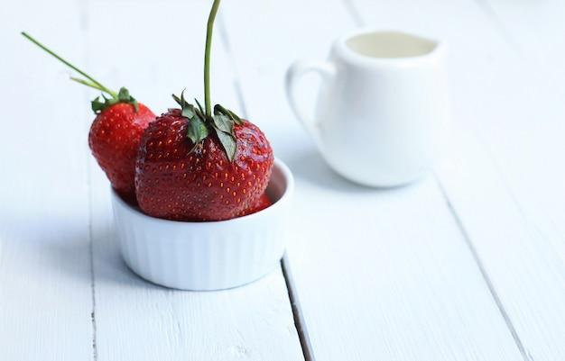 セラミックの白い皿と白いミルク水差しの白い木製の背景にクリームの赤いイチゴ。
