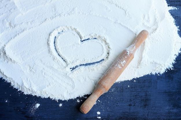 Сердце обращается на муку на столе. рядом есть скалка. концепция приготовления с любовью.