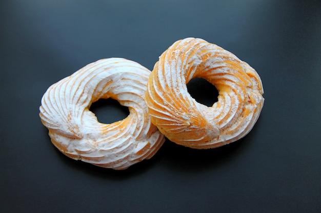 Две круглые профитроли, посыпанные сахарной пудрой на темном фоне