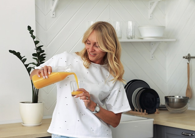 オレンジジュースと台所でガラスを持つ笑顔の女性のクローズアップ。