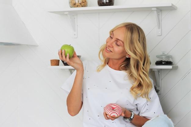 健康的な果物対フィットネスの甘いジャンクフードの誘惑で彼女の手でリンゴとドーナツを保持している女性