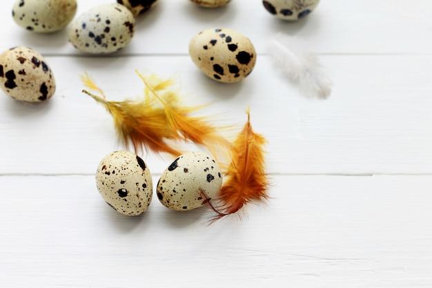 木製の背景にオレンジ色の羽を持つウズラの卵。イースター休暇の背景。