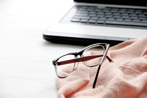 ノートパソコン、メガネ、白い背景の上の女性のスカーフ