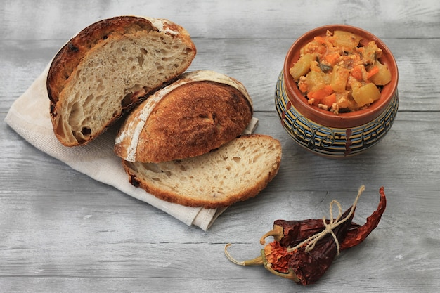 チリコンカルネ。鍋に肉を入れた野菜の煮込み、茶色のパン、唐辛子