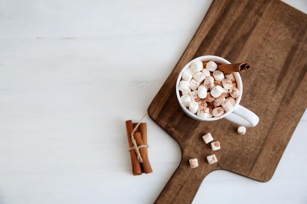Вид сверху кружки с горячим шоколадом и зефиром на разделочную доску рядом с корицей.