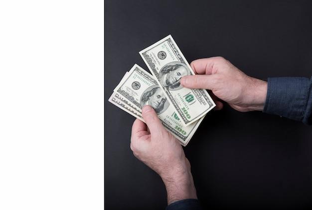 ビジネスの男性の手はお金のために働きます。ドルを数えます。