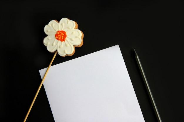 紙、鉛筆、ジンジャーブレッド、白い背景の上の棒に花の形で