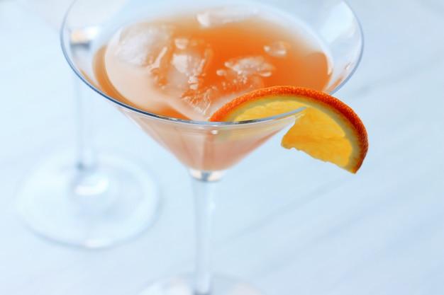 オレンジ色の光の背景の上面のガラスの端にガラスの氷とカクテル