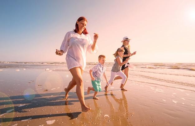 Красивая мама играет со своими детьми в море