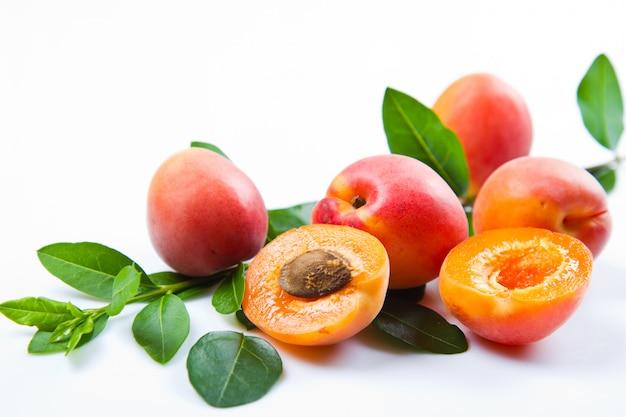 Свежие абрикосы с листьями на белом