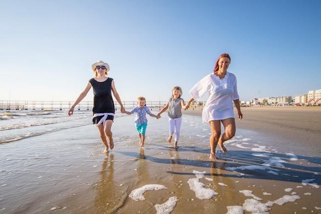 Красивые мамы играют со своими детьми в море