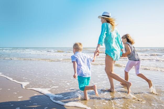 Мать и ее дети играют на пляже