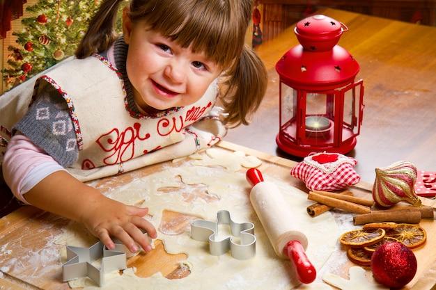 Маленькая девочка, пекущая рождественское печенье