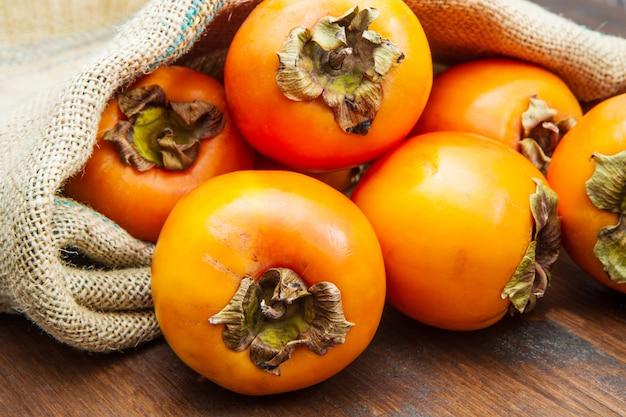 木製のテーブルに美味しい新鮮な柿の果実