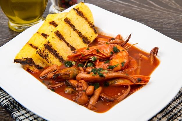 白い皿に焼きポレンタと魚のスープ