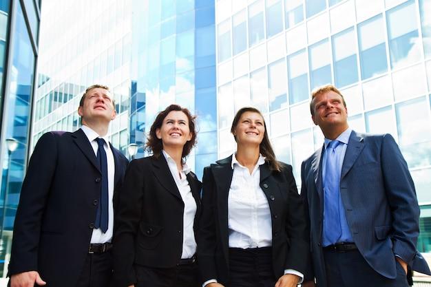 夢のような表情で見上げる幸せなポジティブビジネスグループ