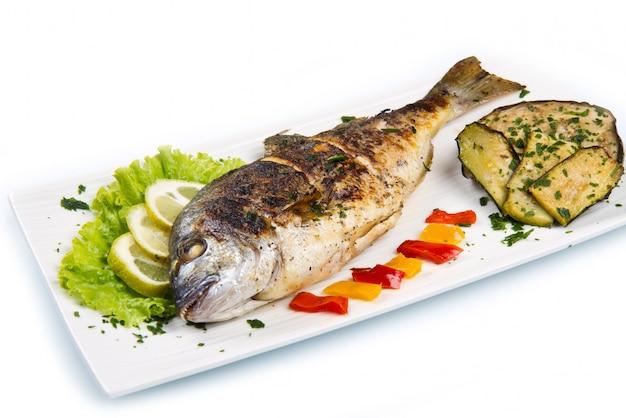 焼き鯛の頭鯛の皿の上のレモン、サラダ、グリル