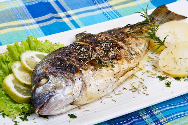 焼き鯛の頭鯛のプレートにレモンとローズマリーとジャガイモ。