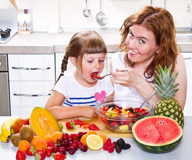 Мама дает маленькой девочке фруктовый салат на кухне.