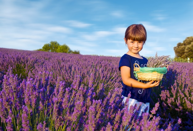 幸せな女の子はラベンダー畑に花のバスケットを保持しています