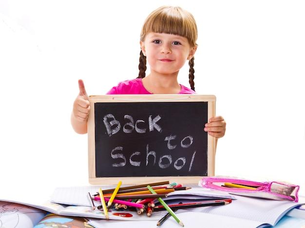 Счастливый улыбающийся школьник держит маленькую доску с текстом «обратно в школу»