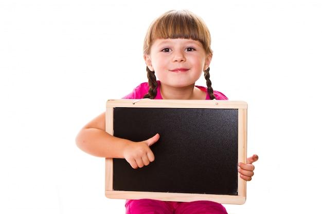 白い背景にブラックボードを保持している小さな女の子