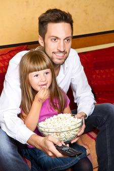 Маленькая девочка и ее приятель любят есть попкорн и смотреть телевизор