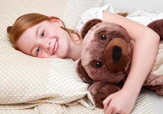 Маленькая девочка в постели, обнимая плюшевого мишку