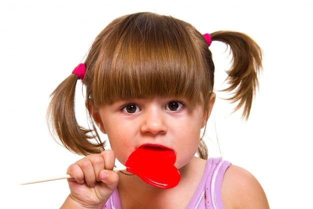 赤いハートのロリポップを食べる少女