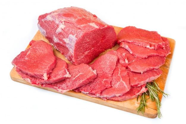 巨大な赤身の肉の塊とステーキの木のテーブル
