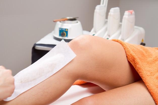 美容師の女性の足をワックス