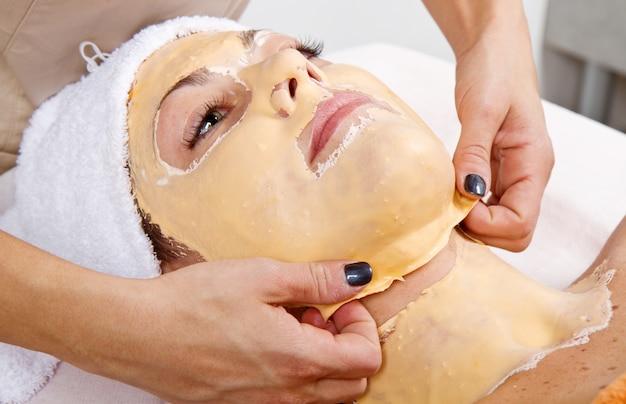 美しい若い女性はビューティーセンターで顔のマスクを削除します