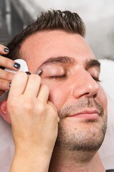 美容院でピンセットで美しい男の眉毛を摘採美容師