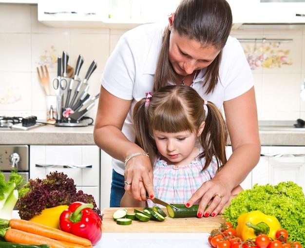 野菜を準備する台所で母と娘