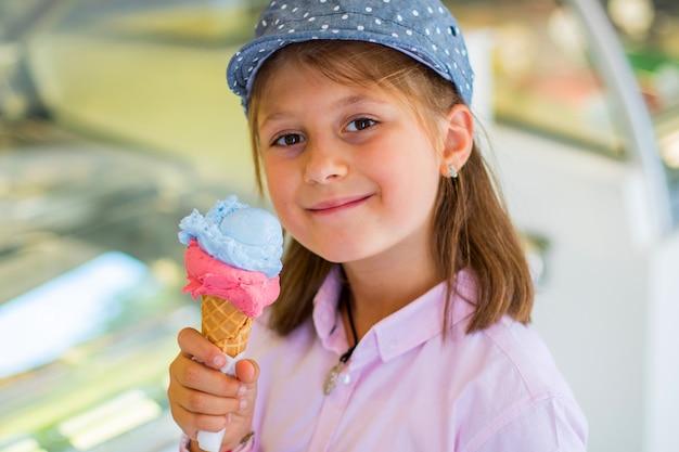 屋外アイスクリームを食べる帽子の美しい少女