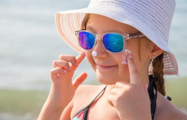 帽子と微笑んでいる女の子がビーチで保護フェイスクリームを塗ります