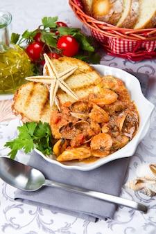 鍋に焼きパンと魚のスープ