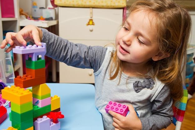 小さな女の子は建物のレンガで遊んでいます。